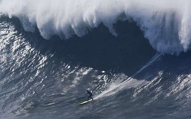 A surfer drops under the lip of a crashing wave face in the semifinals of the Mavericks Surf Contest in Half Moon Bay on Saturday. Photo: Adam Lau, The Chronicle