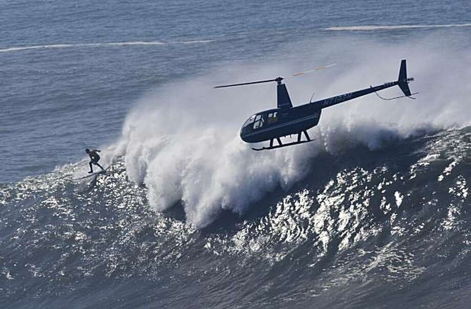 A helicopter hovers nearby as a surfer drops into a wave during hte semifinals of the Mavericks Surf Contest in Half Moon Bay on Saturday. Photo: Adam Lau, The Chronicle