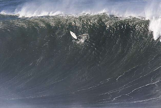 A stray surfboard coasts up a wave face alone during the first round heats of the Mavericks Surf Contest in Half Moon Bay on Saturday. Photo: Adam Lau, The Chronicle