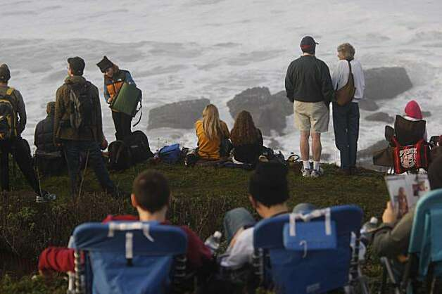 Fighting to see through fog, early risers watch the Mavericks Surf Contest from the cliffs on Saturday Feb. 13, 2009 in Pillar Point, Calif. Photo: Mike Kepka, The Chronicle