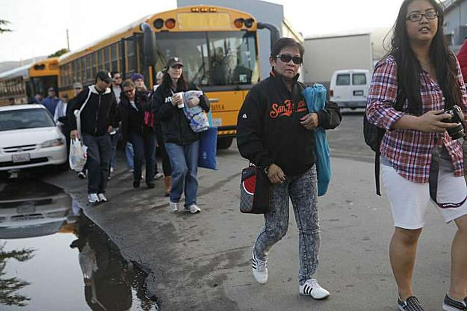 After riding a shuttle bus, Imelda Tilan of San Francisco heads for the beach to watch the Mavericks Surf Contest on Saturday Feb. 13, 2009 in Pillar Point, Calif. Photo: Mike Kepka, The Chronicle