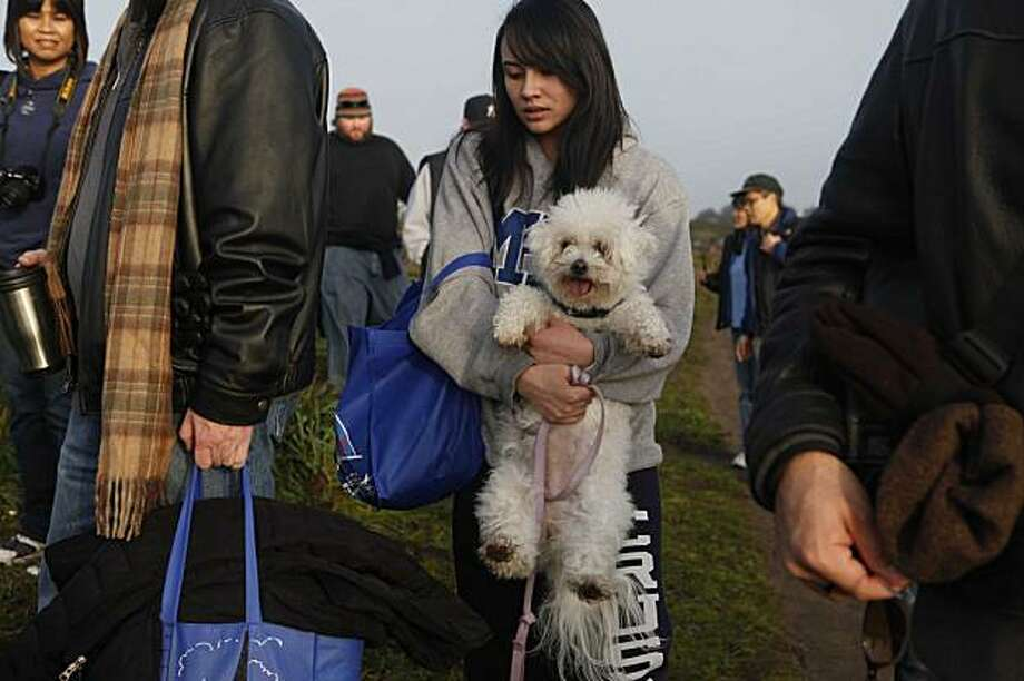 Hoping not get her dog Kona dirty, Celine Castillo, 16, struggles while hiking up the cliffs to watch the Mavericks Surf Contest on Saturday Feb. 13, 2009 in Pillar Point, Calif. Photo: Mike Kepka, The Chronicle