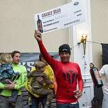 Anthony Tashnick, Santa Cruz native and past Mavericks winner, holds up his check after winning the heaviest wipeout award at the 2009/2010 Mavericks Surf Contest in Half Moon Bay, Calif. on Saturday, Feb. 13, 2010.