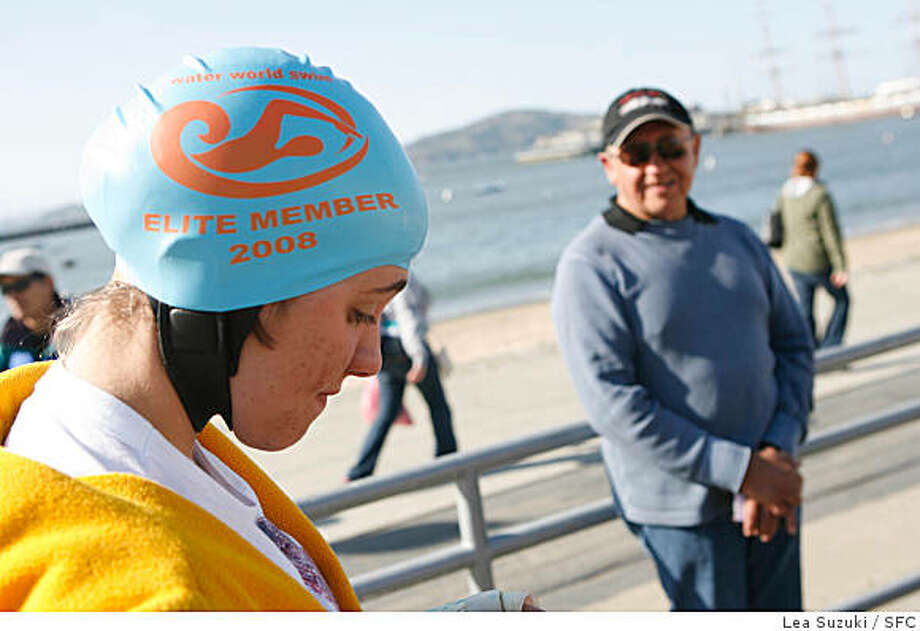 Delia Salomon, 15, prepares for a swim at Aquatic Park on Wednesday April 30, 2008 while watched by Pedro Ordenes (right), her open swim coach. Salomon who dreams of swimming the English Channel will make the attempt in August after she turns 16.Photo By Lea Suzuki/ San Francisco Chronicle Photo: Lea Suzuki, SFC