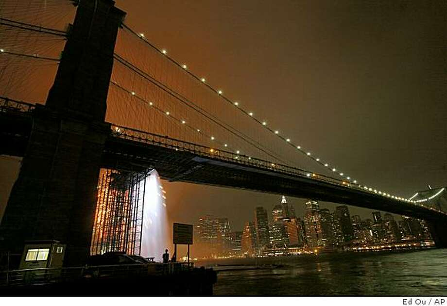 ** FILE ** In this July 4, 2008, file photo, one of the New York City Waterfalls by artist Olafur Eliasson, left, is seen as the Manhattan skyline is backlit by fireworks during the annual Fourth of July display. (AP Photo/Ed Ou, File) Photo: Ed Ou, AP