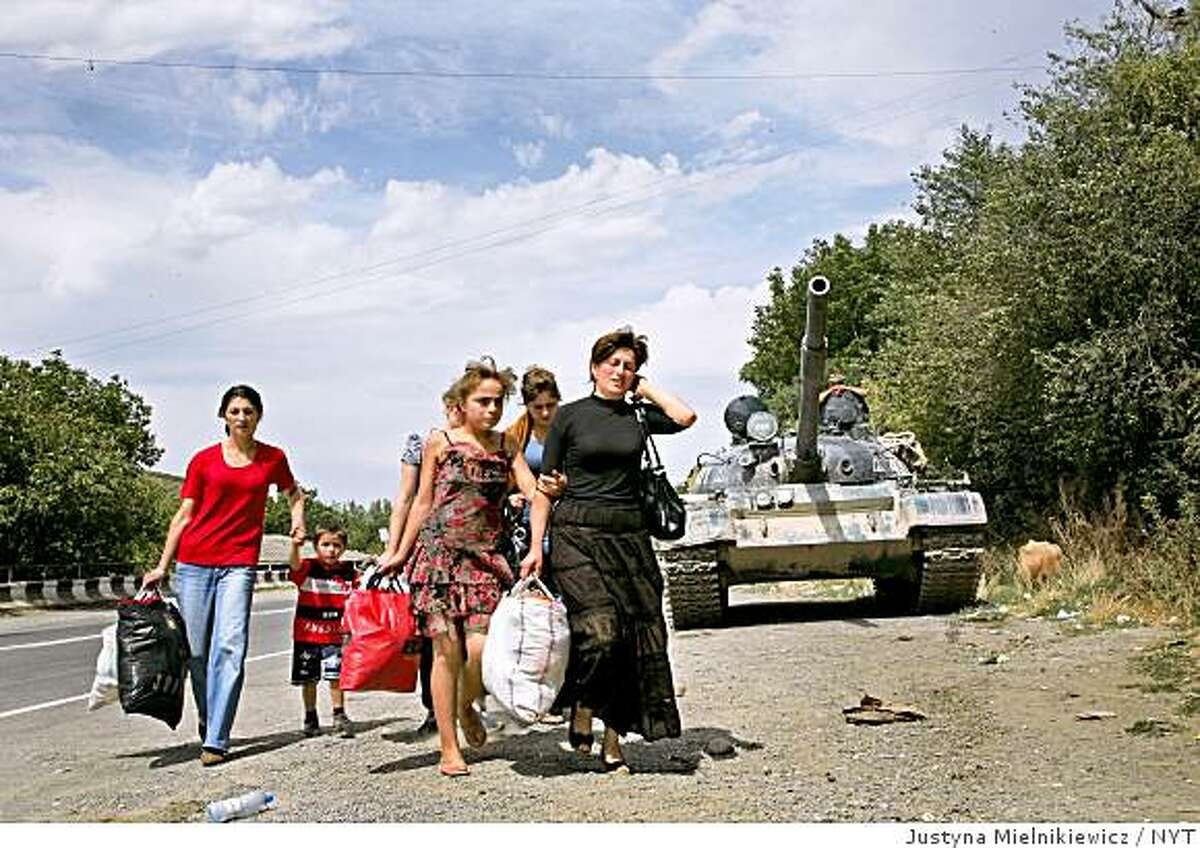 (NYT38) IGOETI, Georgia -- Aug. 16, 2008 -- RUSSIA-GEORGIA-3 -- Georgians from Gori leaving towards Tbilisi as they passing by Russian tank in Igoeti, Georgia, Saturday, Aug. 16, 2008. A day after the American secretary of state Condoleezza Rice went to Georgia, not far from the front lines, to press for immediate withdrawal of Russian forces there, the Kremlin announced on Saturday that it had approved a framework for a cease-fire. (Justyna Mielnikiewicz/The New York Times)