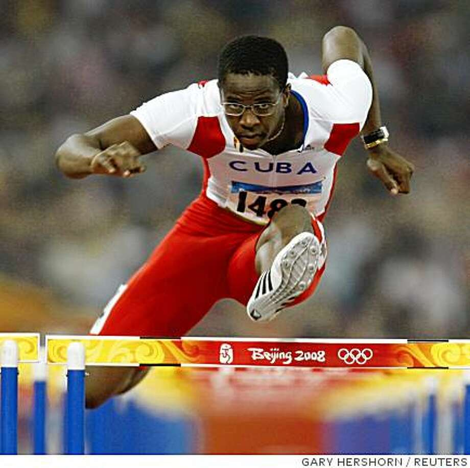Dayron Robles of Cuba clears a hurdle during his men's 100m hurdles heat of the athletics competition at the Beijing 2008 Olympic Games in the National Stadium August 19, 2008.     REUTERS/Gary Hershorn (CHINA) Photo: GARY HERSHORN, REUTERS