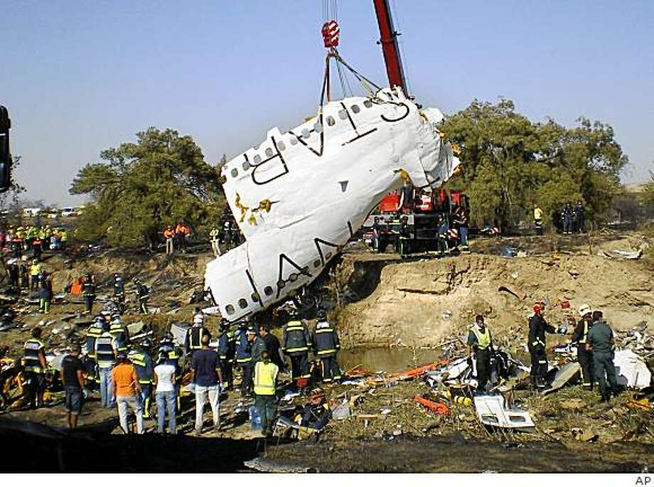 A part of the fuselage of the Spanair jet that crashed on take off at Madrid airport is lifted by a crane on Wednesday, Aug. 20, 2008. A Spanair airliner bound for the Canary Islands at the height of the vacation season crashed, burned and broke into pieces Wednesday while trying to take off from Madrid, killing 149 people on board, officials said. There were only 26 survivors in the mid-afternoon crash, said Spanish Development Minister Magdalena Alvarez, whose department is in charge of civil aviation. It was Spain's most deadly air disaster in more than 20 years. (AP Photo/EFE) **  LATAM, CARIBBEAN AND SPAIN OUT ** Photo: AP
