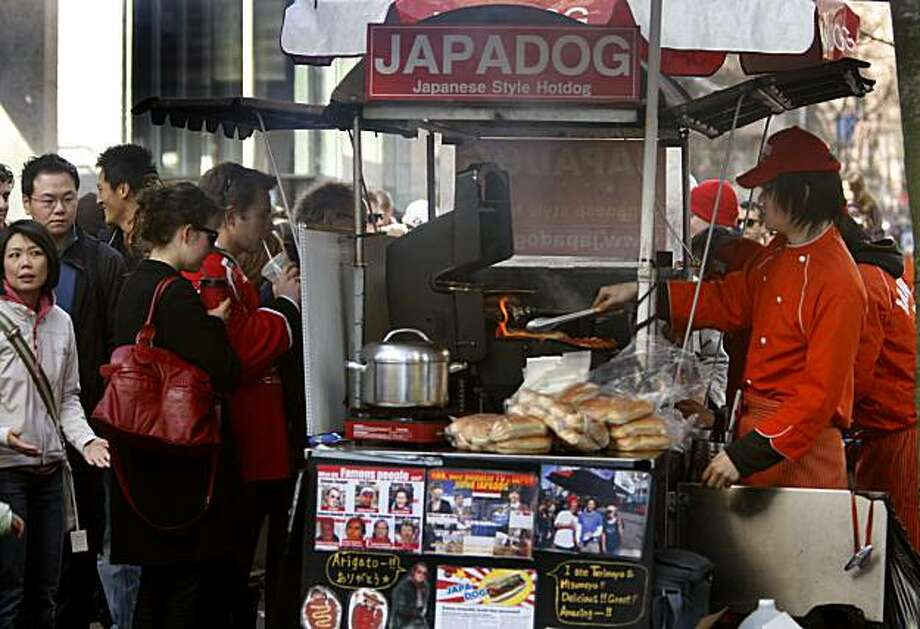 A long line of hot dog lovers wait to place their order at a Japadog stand at Pender and Burrard streets in downtown Vancouver, British Columbia, on Saturday. Photo: Paul Chinn, The Chronicle