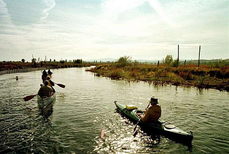This Oct. 4, 1999 file photo shows canoeists paddling along a section of the Wood River near Fort Klamath, Ore., where work has been done to restore the waterway to its original channel. Scientists and policy makers are gathering in Medford, Ore., starting Tuesday, Feb. 2, 2010 to share the latest ecological science on the Klamath Basin and charting new research to help inform a $1 billion restoration plan that includes removing hydroelectric dams that block salmon. Photo: Jeff Barnard, AP