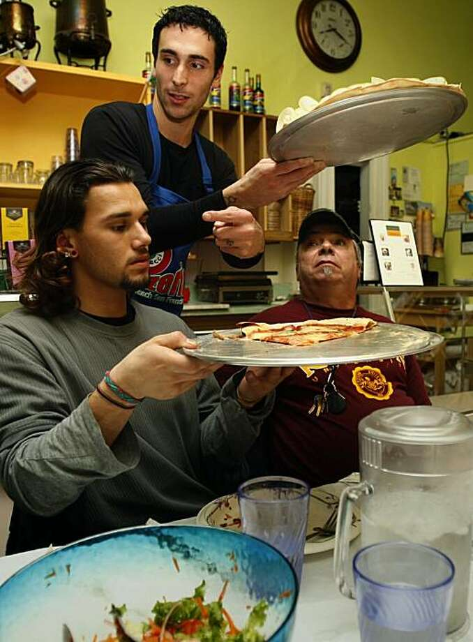 Elia Gambaccini (top) serving a pear pizza with Franki Lopez (bottom, left) and Franky Euphrate (right) watching an italian movie at Caffe Bao Necci in San Francisco, Ca., on Thursday, January 14, 2010. Photo: Liz Hafalia, The Chronicle