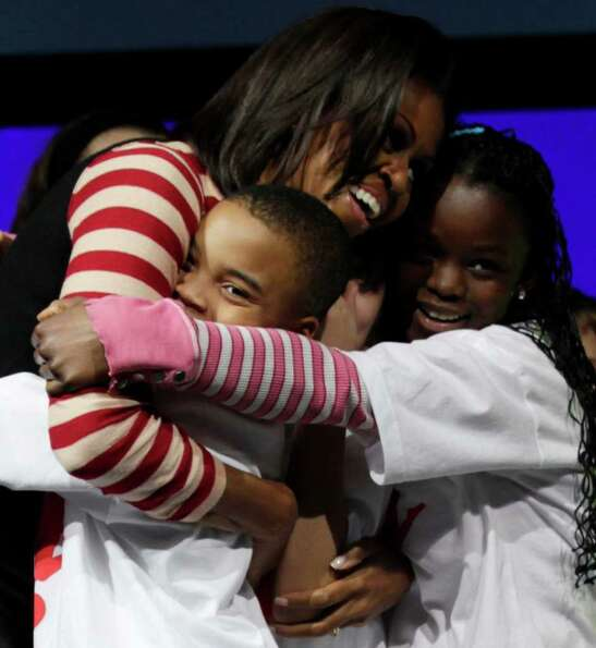 First lady Michelle Obama hugs her dance partners after doing the Interlude dance during a Let's Mov