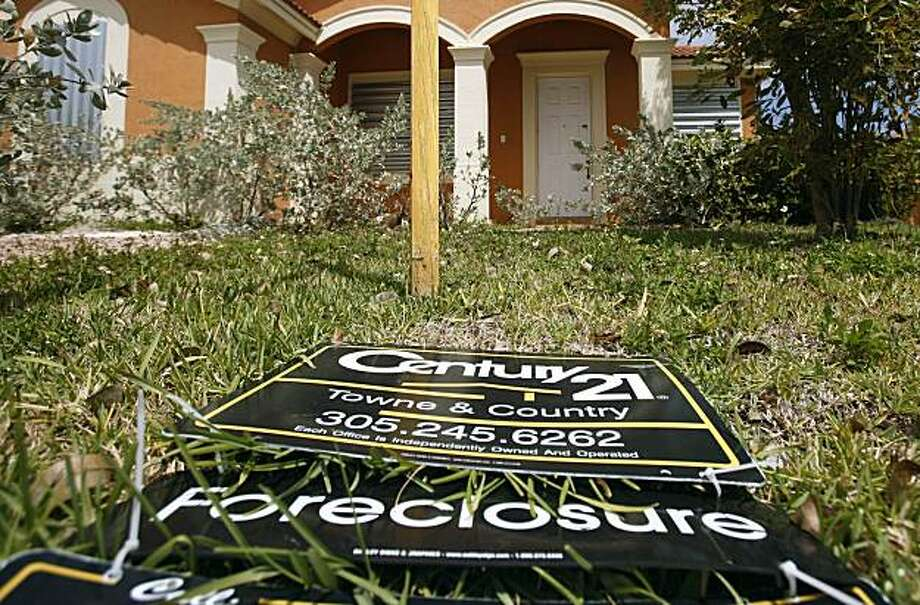 FILE - In this  March 24, 2009 file photo, a sign lies on the ground in front of a foreclosed home in Homestead, Fla. The number of borrowers falling behind on their mortgage payments dropped sharply at the end of 2009, a sign the foreclosure crisis is beginning to ebb. Photo: J Pat Carter, AP