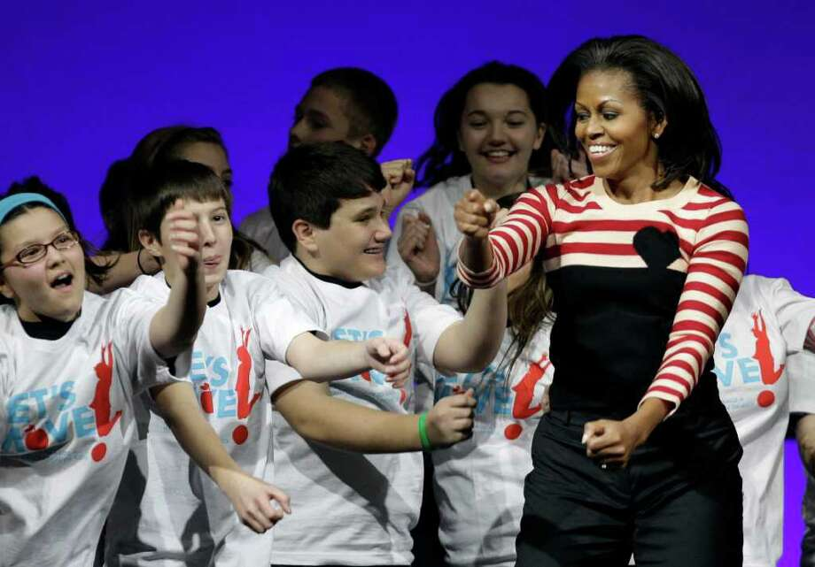 First lady Michelle Obama dances the interlude after speaking at a Let's Move! rally with Iowa students, Thursday, Feb. 9, 2012, at Wells Fargo Arena in Des Moines, Iowa.(AP Photo/Charlie Neibergall) Photo: Charlie Neibergall, Associated Press / AP