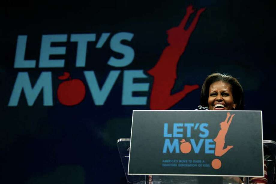 First lady Michelle Obama participates in a Let's Move event with children from Iowa schools, Thursday, Feb. 9, 2012, at the Wells Fargo Arena in De Moines, Iowa, during her three day national tour celebrating the second anniversary of Let's Move.  (AP Photo/Carolyn Kaster) Photo: Carolyn Kaster, Associated Press / AP