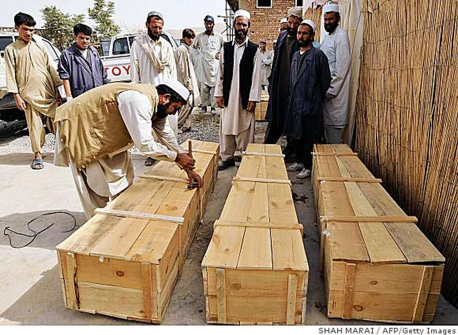 An Afghan hospital worker locks the coffins of three International aid workers killed in an attack claimed by the insurgent Taliban in Logar province some 50 km south of Kabul on August 13, 2008. Three female international aid workers and their Afghan driver were shot dead on August 13 by gunmen who opened fire on their vehicle near the capital Kabul, Afghan authorities said. The killing, claimed by the insurgent Taliban, was the deadliest in years involving international aid workers and comes amid warnings about deteriorating security, said to be at its worst since the 2001 ouster of the Taliban regime. Afghan police said the women were Canadian, Irish and US nationals but this could not immediately be confirmed by the relevant embassies or their employer, the International Rescue Committee (IRC).  AFP PHOTO/SHAH Marai (Photo credit should read SHAH MARAI/AFP/Getty Images) Photo: SHAH MARAI, AFP/Getty Images