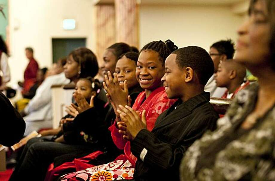 "Jasmine Turner, age 11, (center) and Larry Oliver, age 11, (right) attend a service at the Greater Saint John Missionary Baptist Church in Oakland, Calif., on Sunday, February 14, 2010.  The service included a speech by Mohammad Qayoumi, President of California State University, East Bay, as part of the university system's ""Super Sunday"" program, intended to encourage African American families to prepare their children for college. Photo: Laura Morton, Special To The Chronicle"