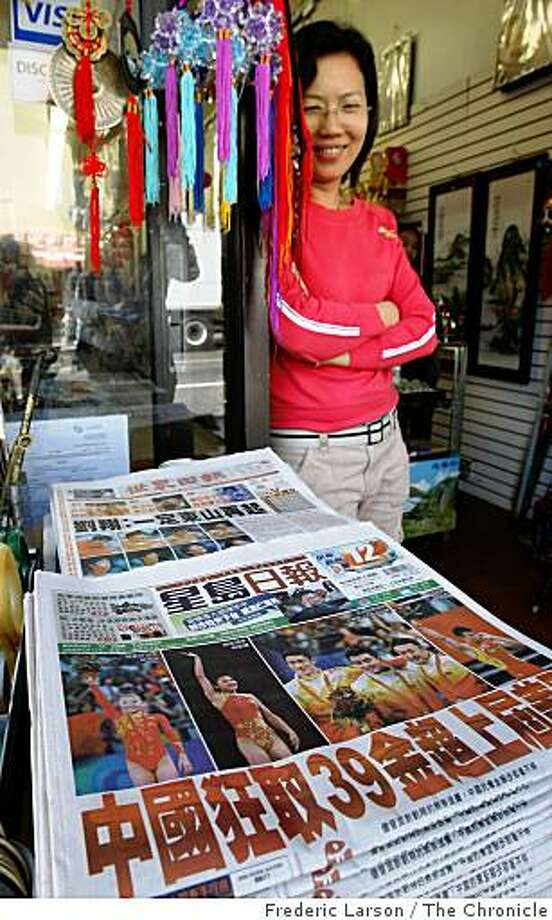 "Hilda (Caiqin) Lin of the Golden Star Sports store on Broadway near Stockton in San Francisco's Chinatown displays China's newspaper ""The Sing Tao Daily"" which headlines that China has surpassed the United States with 39 gold metals in the summer Olympics on August 19, 2008. Photo: Frederic Larson, The Chronicle"
