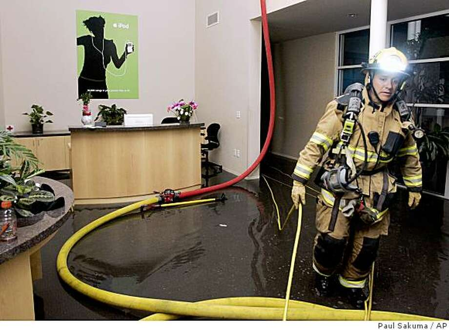 A fireman walks through a lobby soaked with water at Apple headquarters in Cupertino, Calif., early Wednesday, Aug. 13, 2008. Firefighters battled a three-alarm fire that started late Tuesday, Aug. 12, 2008. (AP Photo/Paul Sakuma) Photo: Paul Sakuma, AP