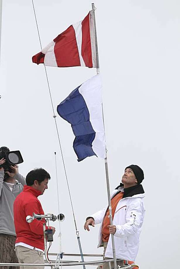 A member of the jury of the 33rd America's Cup, right, puts the flag to signal the postponement of the first race between Swiss defender Alinghi and US challenger BMW Oracle off the coast of Valencia, Spain, on Monday, Feb. 8, 2010. Photo: Victor R. Caivano, AP