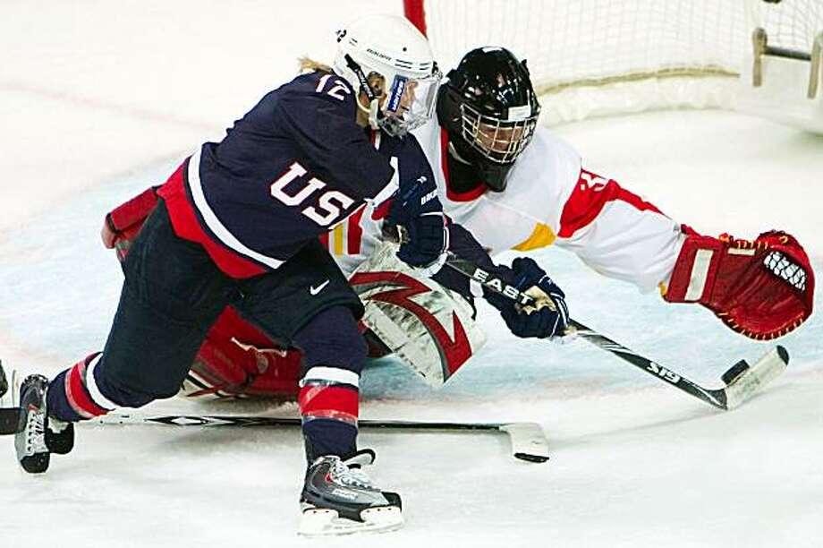 USA forward Jenny Potter slips the puck past China goalie goalie Yao Shi during first period action in women's hockey at the 2010 Winter Olympics at the University of British Columbia on Sunday, Feb. 14, 2010, in Vancouver.  Potter had a hat trick before the game had reached the midway point.  ( Smiley N. Pool / Chronicle Olympic Bureau ) Photo: Smiley N. Pool, Chronicle Olympic Bureau