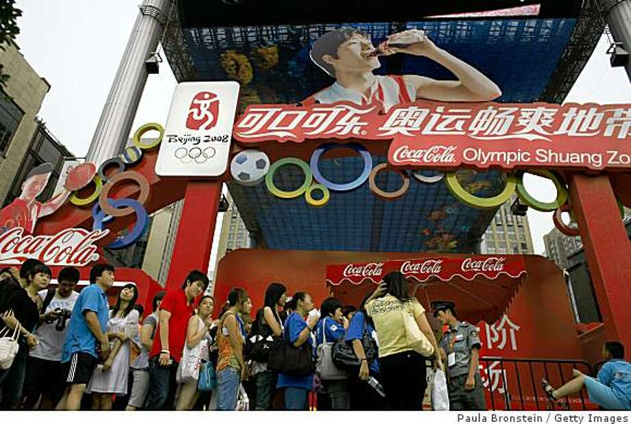 BEIJING, CHINA - AUGUST 19: People wait in line at the Olympic Shuang Zone as Chinese hurdler Liu Xiang, sponsored by Coca Cola, is seen drinking the soda on a billboard August 19, 2008 in Beijing. According to Xinhua agency, Liu Xiang has said he will run even faster after he fully recovers from a tendon injury that forced the Olympic champion out of the Beijing Olympics on Monday disappointing his many fans.  (Photo Paula Bronstein/Getty Images) Photo: Paula Bronstein, Getty Images