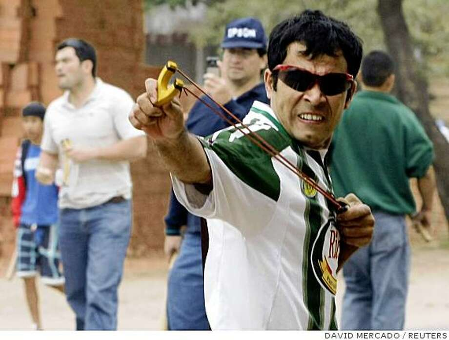 "An anti-government demonstrator uses a slingshot during a strike at the Che Guevara street in the popular quarter ""Plan 3000"" in Santa Cruz, August 19, 2008. Provinces of Santa Cruz, Beni, Pando, Tarija and Chuquisaca called for general strikes demanding autonomy from the central government of President Evo Morales and a greater cut of the country's booming energy revenues. REUTERS/David Mercado   (BOLIVIA) Photo: DAVID MERCADO, REUTERS"