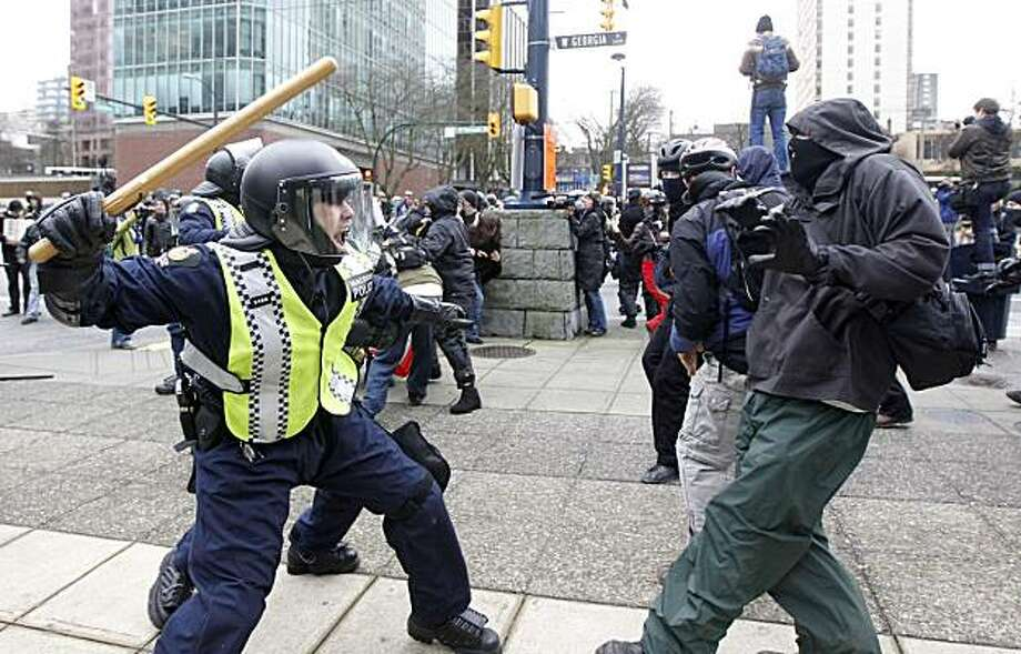 A policeman wields a baton at a protester in downtown Vancouver, British Columbia during the second day of the 2010 Vancouver Olympic Winter Games, Saturday Feb. 13, 2010. Photo: Nathan Denette, AP