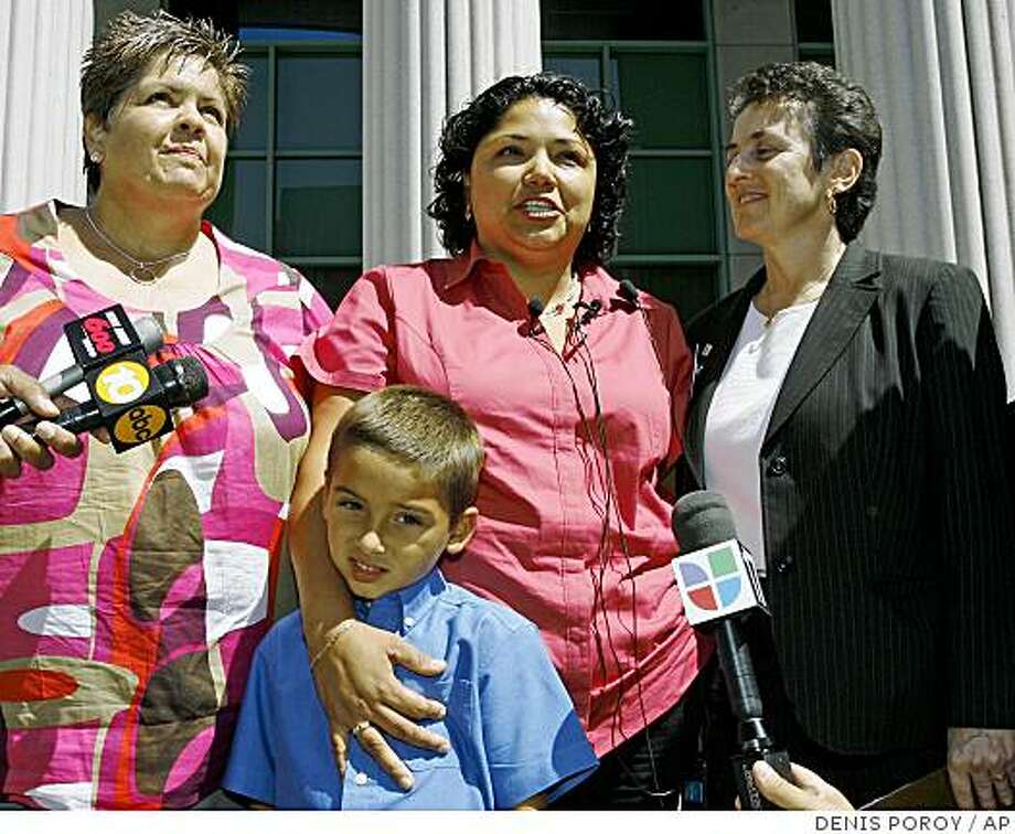 Guadalupe Benitez, center, speaks next to her partner Joanne Clark, left, her son Gabriel Clark-Benitez, foreground, and her attorney Jennifer Pizer, right, at news conference held at  the Hall of Justice in downtown San Diego Monday, Aug. 18, 2008.  The California Supreme Court ruled Monday that  Benitez, a lesbian, was unfairly denied a common infertility treatment  by doctors at the North Coast Women's Care Medical Group based on their  religious beliefs.  (AP Photo/Denis Poroy) Photo: DENIS POROY, AP