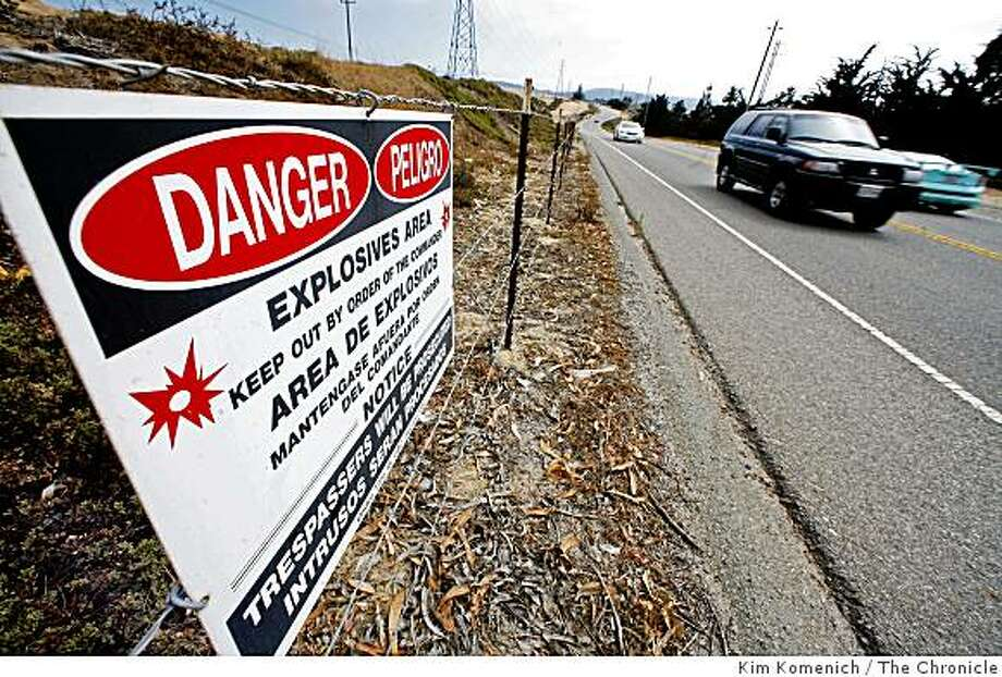 Cars drive by a danger sign on Gen. Jim Moore Blvd. south of Eucalyptus Drive in Fort Ord, Calif.,  on Tuesday, Aug. 12, 2008 on the day officials announced the turning over of more acreage on Fort Ord, for public use. The area inside the fence will be fast-tracked to clear it of unexploded ordnance and make is suitable for public use. Photo: Kim Komenich, The Chronicle