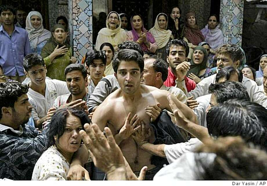 An unidentified relative of a boy shot dead by government forces during a protest is stopped by others as he moves forward to restrain photographers in Srinagar, India, Tuesday, Aug. 12, 2008. Government forces fired at Muslim protesters for a second day Tuesday as they defied a curfew in Indian-controlled Kashmir, killing six, police said. (AP Photo/Dar Yasin) Photo: Dar Yasin, AP