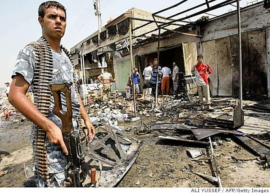 A heavily armed Iraqi policeman keeps an eye on the surroundings at the site of a car bomb explosion that rocked the Baghdad district of Ur, killing six men and wounding eleven others in the early hours of August 16, 2008. The bombing targeted Shiite pilgrims heading to the holy city of Karbala for a religious festival, police and hospital officials said. AFP PHOTO/ALI YUSSEF (Photo credit should read ALI YUSSEF/AFP/Getty Images) Photo: ALI YUSSEF, AFP/Getty Images