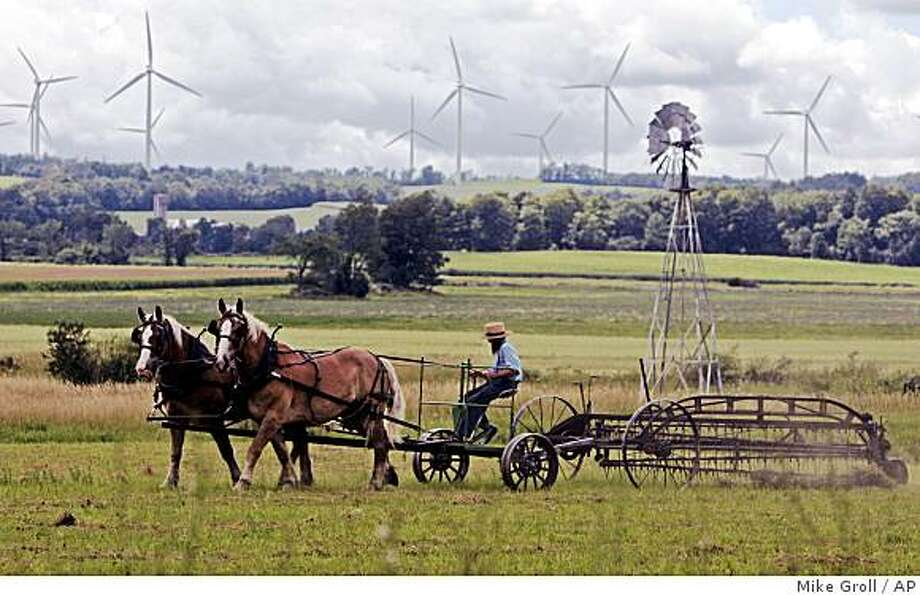 **ADVANCE FOR SUNDAY, AUG. 17**   An Amish farmer rakes hay as wind turbines from the Maple Ridge Wind Farm work in the distance in Lowville, N.Y., Monday, Aug. 4, 2008.  The $400 million Maple Ridge wind project, the largest in New York state, brought money and jobs and a wondrous sense of prosperity to a place that had long given up on any. (AP Photo/Mike Groll) Photo: Mike Groll, AP