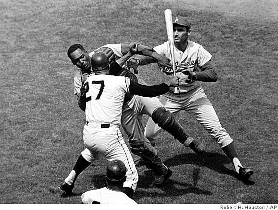 ** FILE ** San Francisco Giants pitcher Juan Marichal (27) swings a bat at Los Angeles Dodgers catcher John Roseboro in the third inning at Candlestick Park in San Francisco, Calif., on Aug. 22, 1965, when Marichal apparently felt Roseboro had thrown too close to his head. Dodgers pitcher Sandy Koufax, rear, tries to break up the fight. Roseboro died after a lengthy illness, a family spokeswoman said Monday, Aug. 19, 2002. He was 69. (AP Photo/Robert H. Houston)Ran on: 05-19-2005Juan Marichal's signature leg kick was not his original motion  --  in the minor leagues, he was actually a sidearm pitcher.Ran on: 05-19-2005Juan Marichal's signature leg kick was not his original motion  --  in the minor leagues, he was actually a sidearm pitcher.ALSO Ran on: 11-25-2007Ran on: 11-25-2007 ** FILE ** San Francisco Giants pitcher Juan Marichal (27) swings a bat at Los Angeles Dodgers catcher John Roseboro in the third inning at Candlestick Park in San Francisco, Calif., on Aug. 22, 1965, when Marichal apparently felt Roseboro had thrown too close to his head. Dodgers pitcher Sandy Koufax, rear, tries to break up the fight. Roseboro died after a lengthy illness, a family spokeswoman said Monday, Aug. 19, 2002. He was 69. (AP Photo/Robert H. Houston) Photo: Robert H. Houston, AP