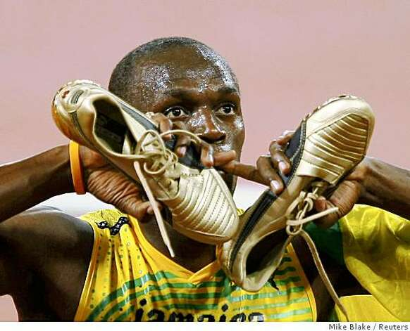 Usain Bolt of Jamaica holds his shoes as he celebrates winning the men's 100m final at the Beijing 2008 Olympic Games August 16, 2008. Photo: Mike Blake, Reuters