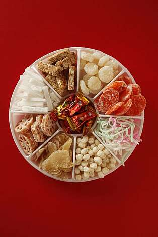 Arrangement of various sweets (candied fruits & vegetables, candies, cookies) for Chinese New Year including: wintermelon, pineapple, carrots, lotus root, lotus seed, ginger, coconut, water chestnut, red melon seeds; red foil-wrapped peanut candy, sesame & peanut candy; puff rice cookies in San Francisco, Calif., on February 3, 2010. Photo: Craig Lee, Special To The Chronicle