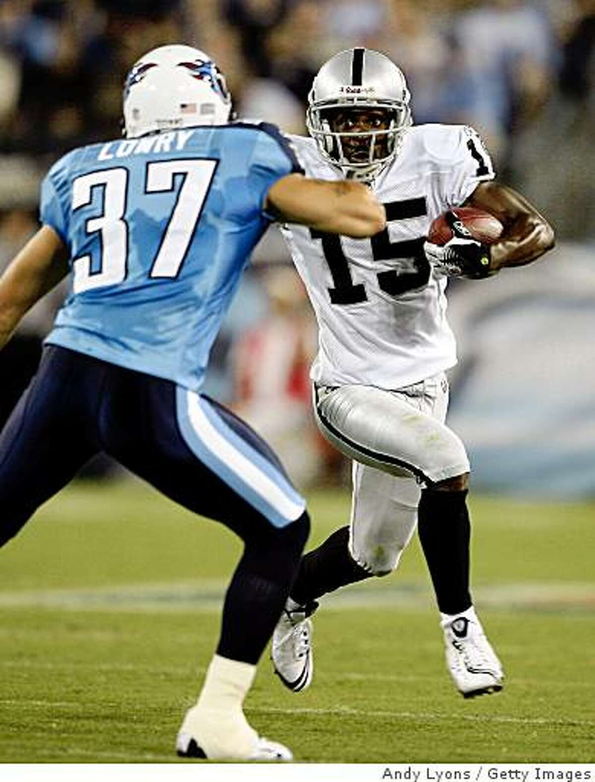 NASHVILLE, TN - AUGUST 15: Johnnie Lee Higgins #15 of the Oakland Raiders runs with the ball against Calvin Lowry #37 of the Tennessee Titans during the NFL pre-season game at LP Field August 15, 2008 in Nashville, Tennessee. (Photo by Andy Lyons/Getty Images)