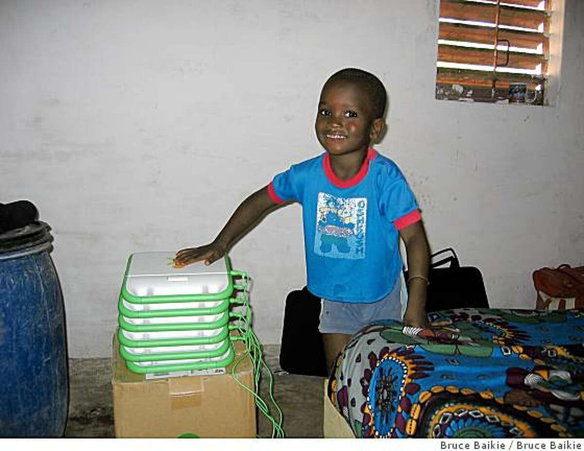 A first year grade school student in Senegal smiles while holding a pile of solar powered laptops.