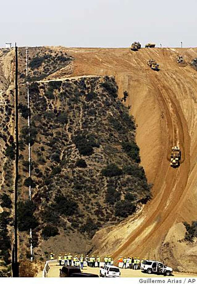 A U.S. construction crew fills the Smuggler's Gulch canyon near the U.S.-Mexico border in San Diego, Calif., Friday, Aug. 15, 2008. Scrapers and bulldozers began filling a deep canyon Friday to make way for a border fence in the southwestern corner of the continental United States after 12 years of planning, environmental reviews and legal challenges (AP Photo/Guillermo Arias) Photo: Guillermo Arias, AP