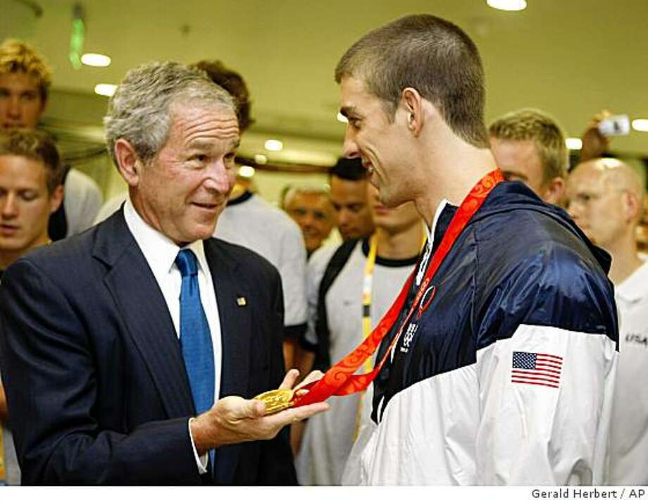 President Bush, greets gold medal and world record winner Michael Phelps after his swimming event at the 2008 Summer Olympic games in Beijing, China Sunday, Aug. 10, 2008.  Phelps had just set a world record in the men's 400 meter medley. (AP Photo/Gerald Herbert) Photo: Gerald Herbert, AP