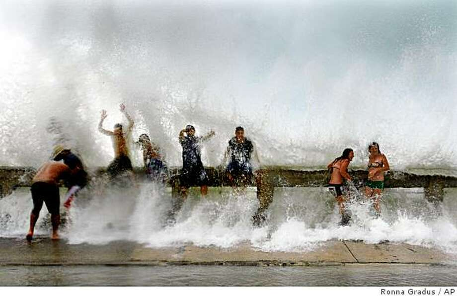 Storm enthusiasts get soaked by waves crashing against the pier  in Key West, Fla.  during Tropical Storm Fay on Monday, Aug. 18, 2008. The National Hurricane Center says the center of Tropical Storm Fay has passed over Key West.  Hurricane forecasters say the center made landfall over the island at 3 p.m. EDT. The storm is expected to strengthen into a possibly Category 1 hurricane before hitting Florida's Gulf Coast sometime Tuesday. Category 1 storms have winds of at least 74 mph.  (AP Photo/Miami Herald,Ronna Gradus)  SOUTH FLORIDA OUT, ORLANDO SENTINEL OUT, NO MAGS, NO SALES Photo: Ronna Gradus, AP