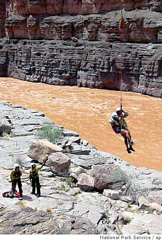In this photo released by the the National Park Service (NPS),  a stranded rafter is lowered to shore by an NPS employee after being  short hauled across the Colorado River Sunday Aug. 17, 2008, in the Grand Canyon after an earthen dam broke. National Park Service / AP Photo: National Park Service, Ap