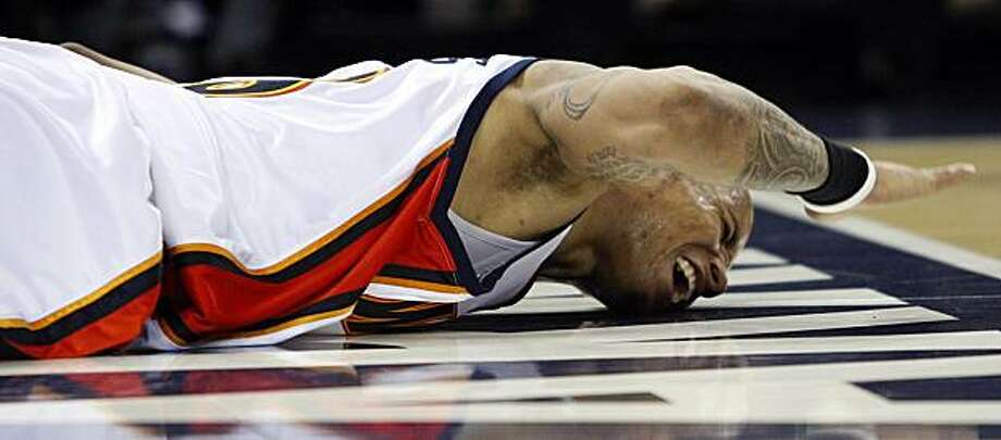 The Golden State Warriors' Monta Ellis yells in pain on the floor during the fourth quarter against the Dallas Mavericks on Monday in Oakland. Photo: Ben Margot, AP
