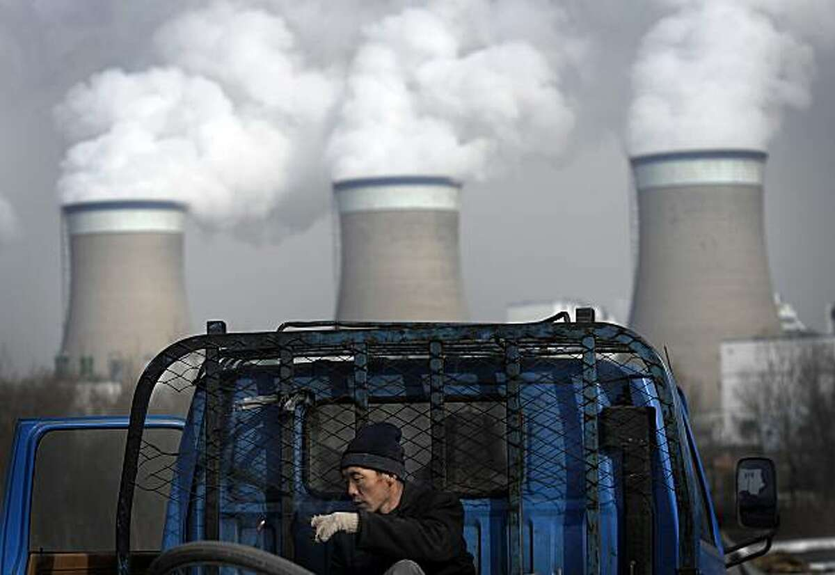 FILE - In this Dec. 3, 2009 file photo, a worker throws his cigarette while smoke on a truck parked in front of a cooling towers of a coal-fired power plant in Datong, Shanxi province, China. China has revealed its most ambitious measure of what explosivedevelopment has done to its environment, saying Tuesday, Feb. 9, 2010. that its first national pollution census has mapped nearly 6 million sources of industrial, residential and agricultural waste.