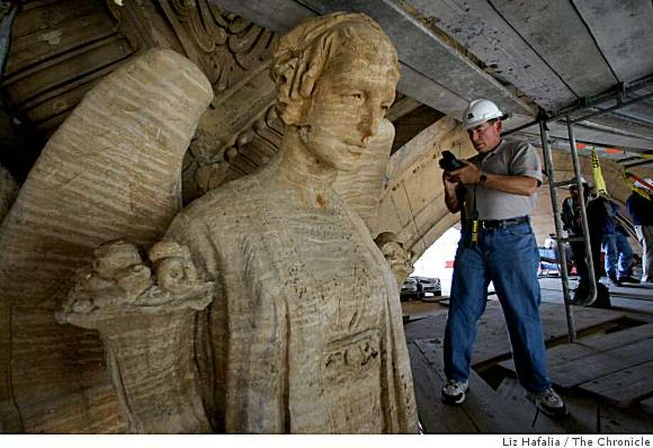 The Palace of Fine Arts in the Marina in San Francisco, Calif. is getting a multi million dollar makover to make it seismically safe as photographer and vice president of the Oakland Museum of Art Rich Edwards on Tuesday, August 12, 2008, takes a picture of one of  eight  15 foot angels atop the columns in the rotunda. Photo: Liz Hafalia, The Chronicle