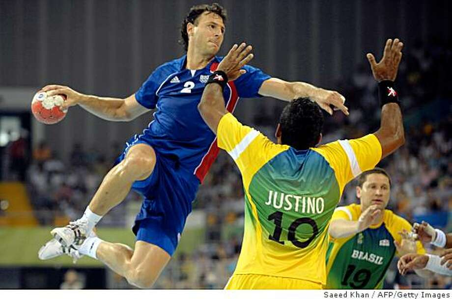 France's Jerome Fernandez (L) jumps to score after dodging Brazil's Helio Justino during their 2008 Olympic Games men's handball match on August 10, 2008. France defeated Brazil 34-26. AFP PHOTO / Saeed KHAN (Photo credit should read SAEED KHAN/AFP/Getty Images) Photo: Saeed Khan, AFP/Getty Images
