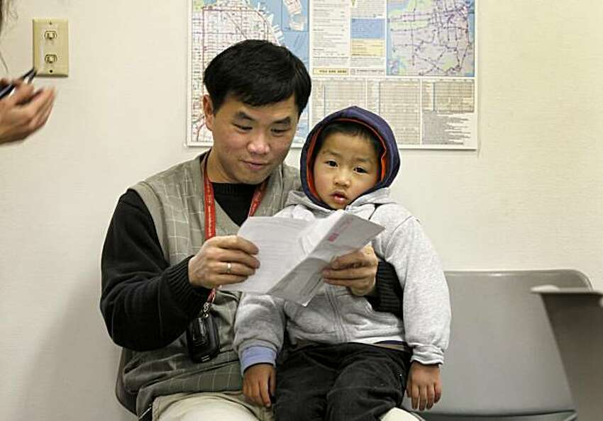 Hung Vinh Huynh (left) held his son Danny as he looked over paper work to sign him up for upcoming kindergarten. Families with school age children in San Francisco, Calif. are currently doing the complicated student assignment process, which decides what school your child attends. Several parents were filling out the papers Thursday February 4, 2010 at the Educational Placement Center.