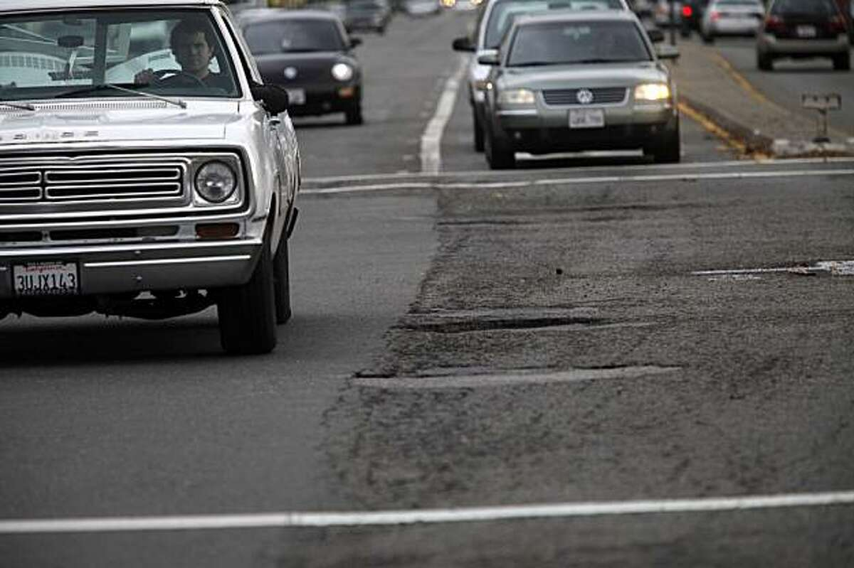 Cars headed over a pot holes and cracked road at Route 185 (Mission Blvd) on Wednesday, Dec. 16, 2009 between San Leandro and Hayward, Calif. The Bay Area's roads are the worst in the country topped only by roads in Los Angeles.