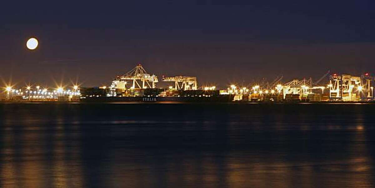 A full moon rises over the Port of Oakland as a container ship is unloaded and reloaded prior to sailing. Aug 6, 2009