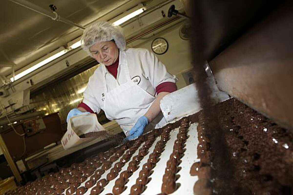 Beatrice Laura, marker operator, shakes sprinkles onto chocolates at the See's Candies, Inc. factory on Tuesday February 9, 2010 in South San Francisco, Calif.